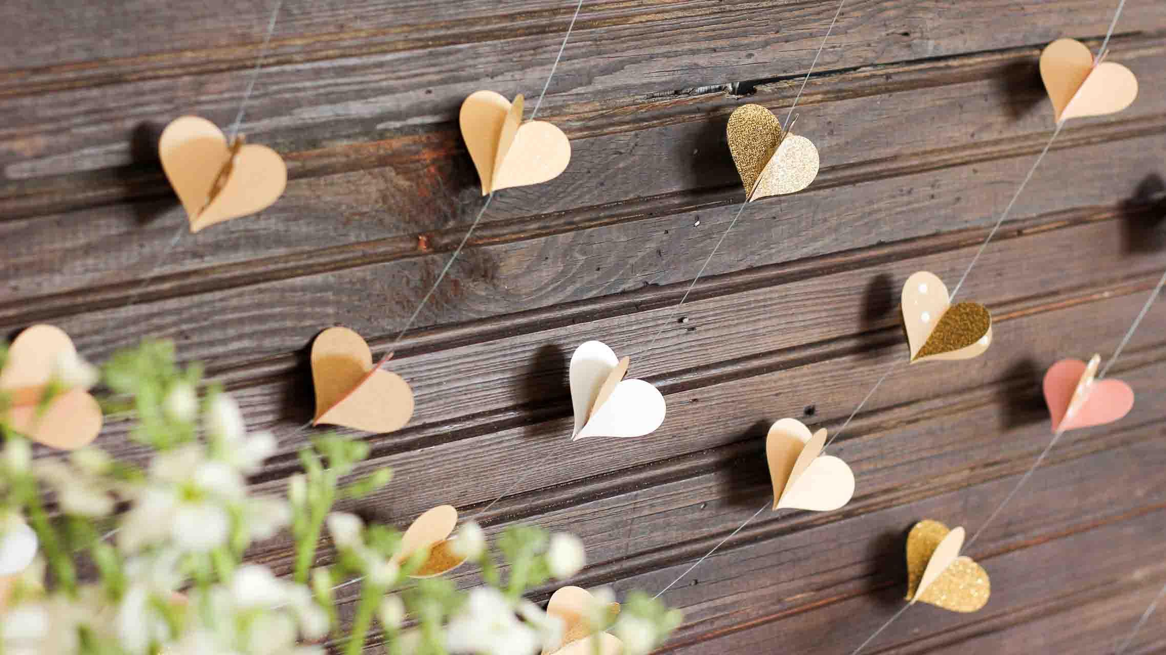 Гирлянду из сердечек можно с легкостью использовать не только для украшения зала на Новый год, но и при подготовке праздника ко Дню влюбленных, или на свадебное торжество