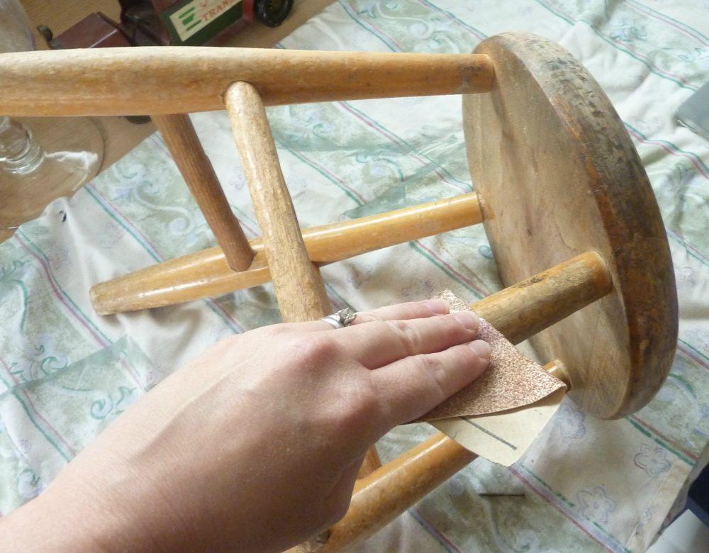 Ошкуривание табурета с помощью наждачки